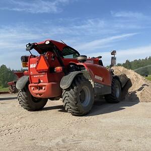 Maskinen är en stark och säker maskin att lyfta med och att köra med last, även på ojämna ytor. Här tar den en rejäl skopa sand för att fylla på dressaren.