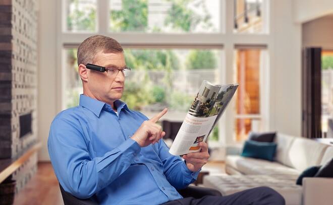 Manden læser blad med OrCam.