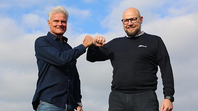 """Ole Wamsler (tv.), adm. direktør i Ajos a/s og Michael Ipsen, adm. direktør i Hejs.dk A/S \""""giver hånd\"""" på frasalget af Ajos hejsafdeling til Hejs.dk."""