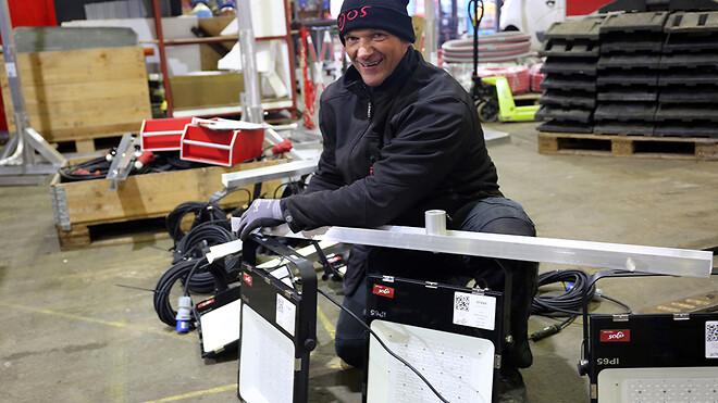Ajos A/S har investeret i en ny type teleskoplysmaster. Her er Sebastian Sakowski, lagermedarbejder i Midlertidige Installationer er ved at klargøre teleskopmaster og lamper på lageret i Hvidovre.
