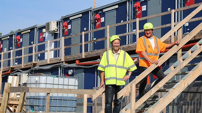 Afdelingschef for skure og moduler Henrik Clausen og driftschef Flemming Madsen foran skurbyen på byggepladsen ved Nyt Hospital Hvidovre, der primært består af de nye mandskabsmoduler med plads til tyve personer.