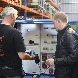Servicemontør Mike Jensen (tv.) tester en tavle med en installationstester, mens el-installatør Ronnie Lindfoss kvalitetssikrer processen.