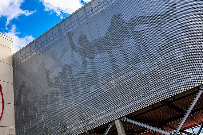 Fasaden återger bilder av träd och silhuetter av jublande fläktar i perforerad metall