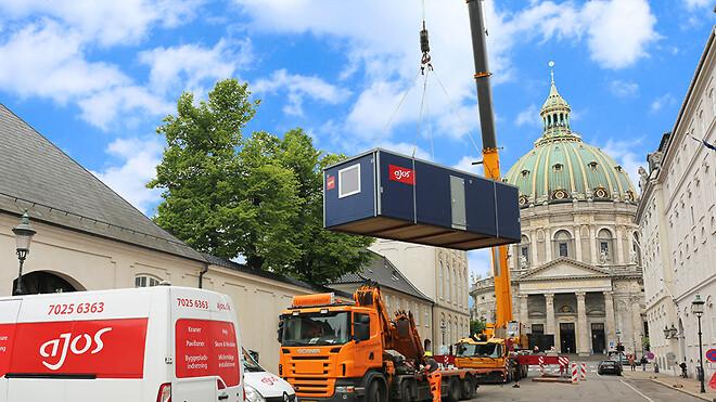 Ajos a/s har til en større renovering af et ældre kontorbyggeri i Bredgade i København leveret og opsat en skurby i en snæver baggård. Alle containere og moduler er blevet løftet cirka 40 meter med en kran ind over eksisterende bygninger.