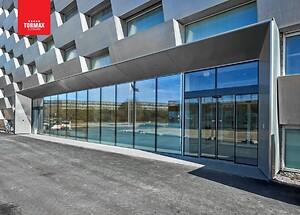 TORMAX Automatisk Skydedør i vindfang. Her udført i structural glazing for et smukt finish.