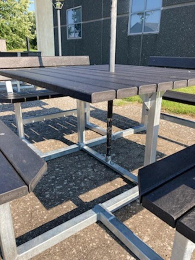 Vi har videreudviklet vores kvadratiske bord-bænke sæt, så nu kan du tilkøbe en parasol fod som tilbehør. Derved kan du sætte din parasol ned i bordet og nyde vejret uden at blive solbrændt. Du behøver derfor ikke at have en parasol stående på fod ved siden af bordet og fylde, da den er inkorporeret.