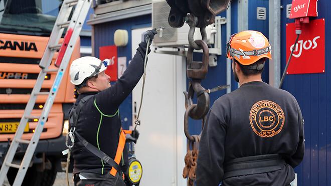 Der bliver ikke taget let på sikkerheden hos Ajos. Her er produktionstekniker Lasse Nørreskov Nielsen fra Ajos skurafdeling fastgjort med sikkerhedsline til en kran, inden han selv fastgør en kæde på skur inden løft.