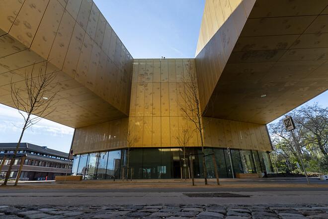 Ved inngangen til hovedkvarteret forbindes tre fløyer av bygningen og danner en bro over en av hovedinngangene til området. Her består fasaden av 385 perforerte aluminiumsplater, som dekker et areal på 1.640m2.