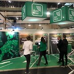 Grøn messestand med loftbanner, messevæg og brochureholder for Bro Bizz