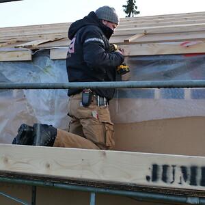 Tømrer arbejder på robuste skæve boliger på Oliefabriksvej