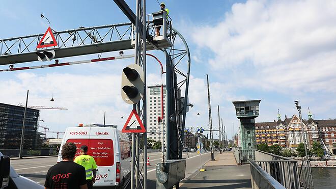 Ajos indledte i midten af august opsætningen af midlertidig belysning på Langebro i København. Her er el-tekniker Torben Steen Nielsen oppe i kurven, mens el-tekniker Martin Iversen og lager- og logistikmedarbejder Regnar Rabe (t.v.) assisterer.