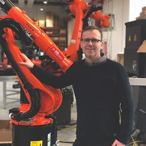 Billede af Michael Friis ved siden af orange KUKA robot