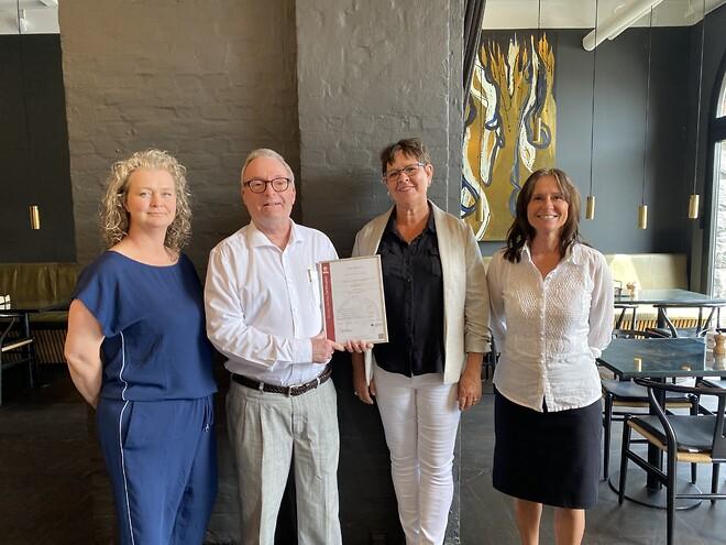 Billedtekst: Michael Fich, Lead Auditor hos Bureau Veritas, overrækker ISO 14001 certifikat til Liselotte Lybæk, Driftsdirektør, Lotte Schantz Christensen, Miljøkonsulent, og Birgitte Bodorf, Kundechef, hos Meyers Kantiner.