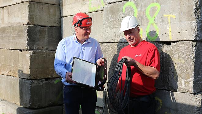 Sektionsleder Jan Frandsen og servicemontør Mike Jensen med en af de nye LED-lamper, der er er lettere at bære og nemmere at montere på masterne end tidligere lamper.