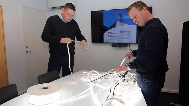 Ajos a/s kan snart tilbyde sine kunder byggepladsbelysning med LED-bånd. Afdelingschef for Midlertidige Installationer Jan Frandsen (tv.) og Mads Christian Petersen, der er leder af klargøring og logistik, tester LED-båndene på kontoret i Køge.