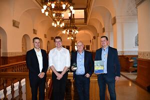 """Energiprisen består bl.a. af bronze-skulpturen, """"Livshjulet"""" af billedhuggeren Jens Ingvard Hansen. Fra højre: Troels Blicher Danielsen, adm. direktør i TEKNIQ Arbejdsgiverne, Rasmus Helveg Petersen (RV), formand for Klima-, Energi- og Forsyningsudvalget, Per Smedegaard, adm. direktør hos Kjærgaard A/S, og Niels Abildgaard, afdelingsleder i Kjærgaard A/S."""