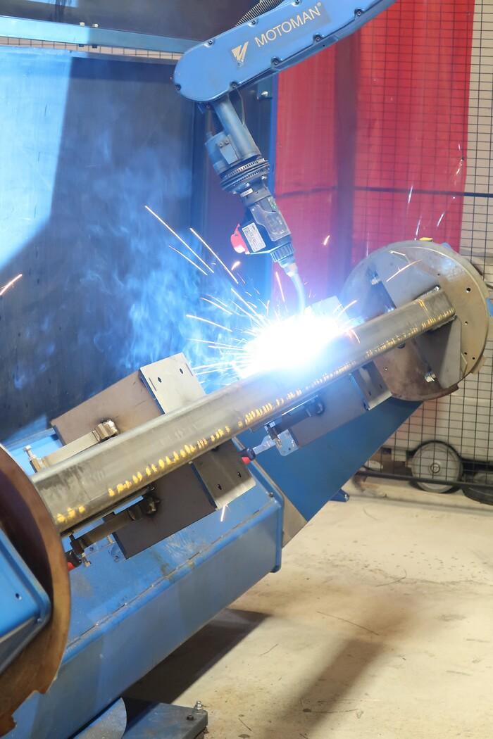 Svejserobotten kan svejse emner på 2,5x1300x1300 mm, og der sidder to manipulatorer på. Den er monteret på en køreskinne i arbejdsområdet og opgraderet med en ny CMT-kilde fra Fronius med mulighed for at svejse rustfri stål, aluminium og sort jern.