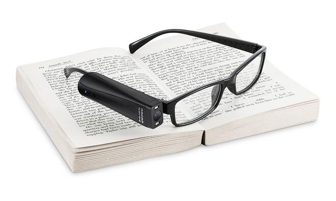 OrCam med brille på bog.