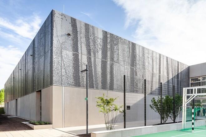 Ved å bruke RMIG ImagerPerf ble et bilde av en vårskog gjenskapt på perforerte metallplater, og dette skaper harmoni mellom skolens arkitektur og det omkringliggende skogområdet