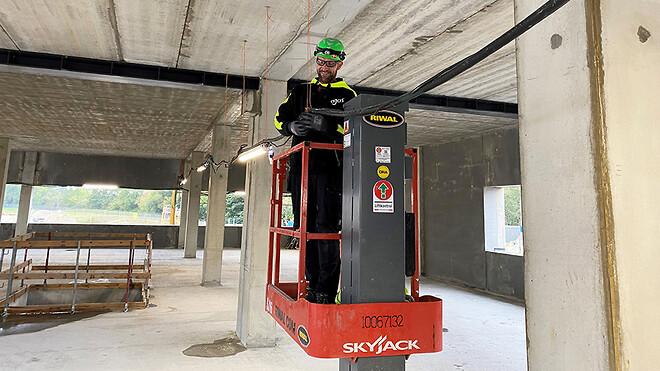 Elektriker Torben Steen Nielsen monterer LED-armaturer indvendigt i byggeriet.