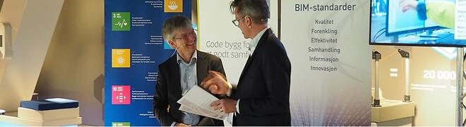Statssekretær Paul Chaffey i Kommunal- og moderniseringsdepartementet får overrakt de to nye BIM-standardene av adm. direktør Jacob Mehus i Standard Norge.