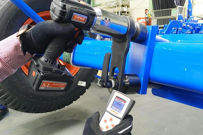 "Picture 1: Wireless handheld digital control ""ADS Smart Control"" manages all relevant application data for one or more ITH Battery Nut Runners type ADS Digital. Pictured above, axle connection bolts of an agricultural machine are precisely tightened to 1.000 Nm (738 ft*lbs)."